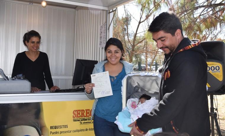 6. Padres de familia exhiben el certificado de nacimiento registrado en la caseta inaugural en Cercado, Cochabamba.