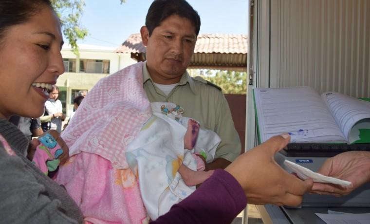 7. Una madre de familia recibe los documentos de su hijo después de registrarla en la caseta registral en Cercado, Cochabamba.