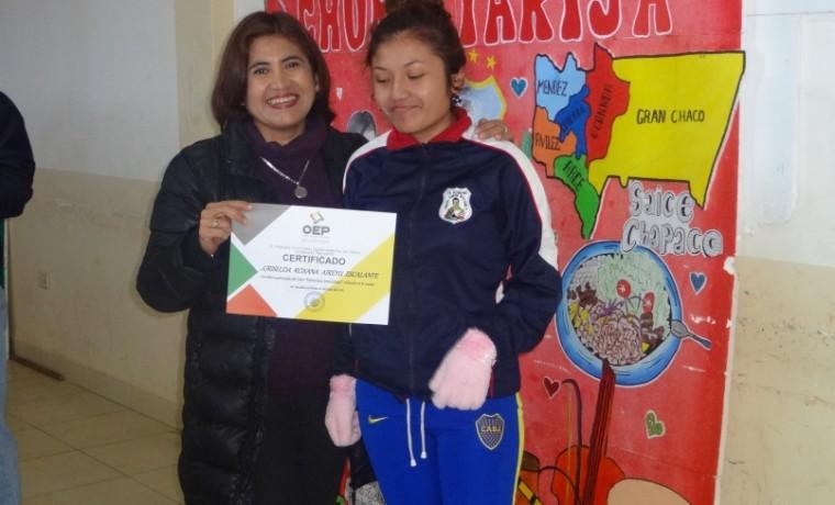 Presidenta del TED Tarija, Cristina Vargas, entrega los certificados de reconocimiento a estudiantes de la unidad educativa Simón Bolívar 4.