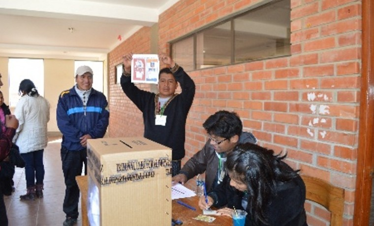 Jurado electoral muestra la papeleta de votación.